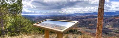 Mesa de interpretación con paisaje nublado al fondo