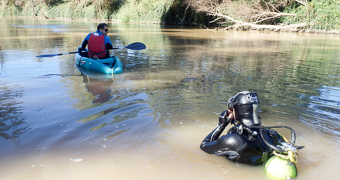 Piragua y buzo prospectando en el río